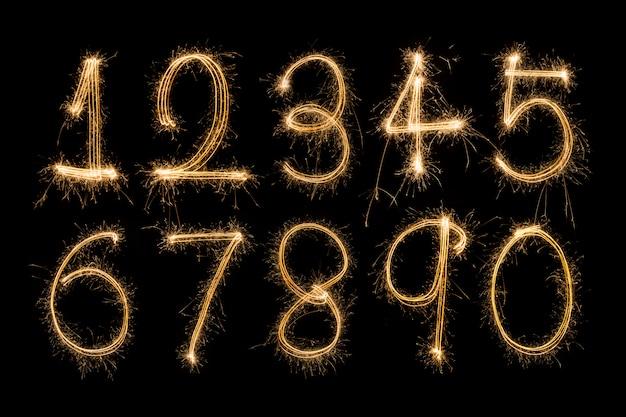 Sparklers di alfabeto e di numeri su priorità bassa nera