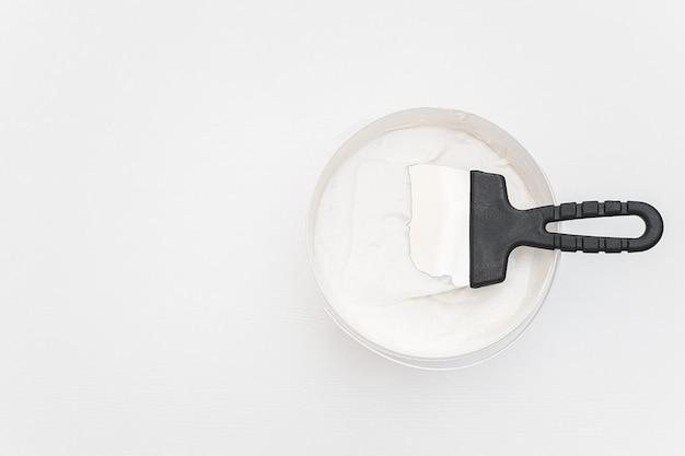 Spatola e un secchio di mastice su assi di legno bianchi.
