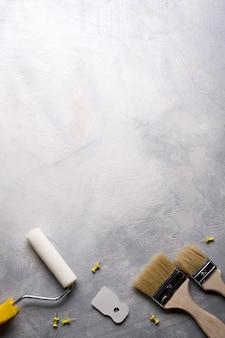 Spatole per l'applicazione di stucco e pennelli e rulli per la pittura su uno sfondo di cemento grigio. vista dall'alto