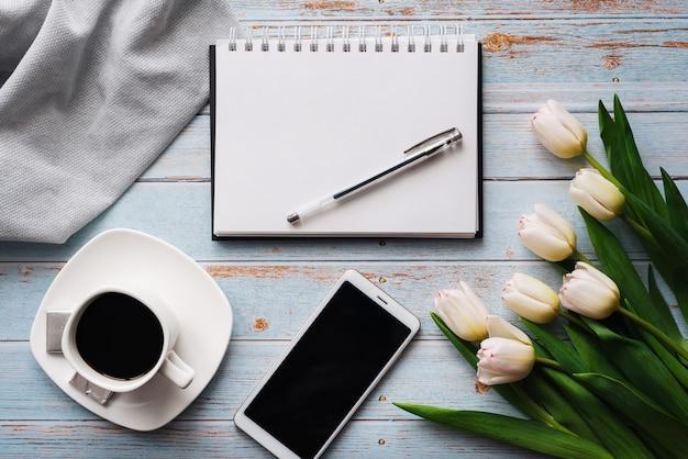 Spazi in bianco della primavera del posto di lavoro di un libero professionista con un mazzo di tulipani bianchi, uno smartphone, un mazzo bianco vuoto e una tazza di caffè in sue mani su fondo di legno