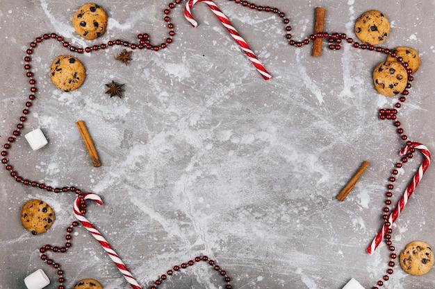 Spazi vuoti all'interno di un cerchio di spezie, biscotti, caramelle bianche rosse e ghirlanda rossa
