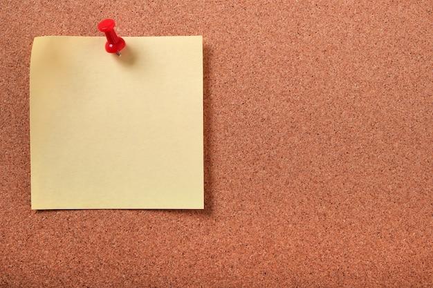 Spazio appuntato della copia del bordo del sughero della nota appiccicosa gialla di posta