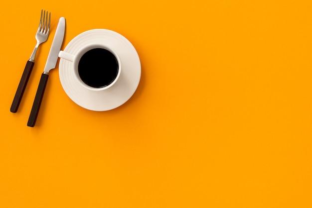 Spazio caffè con forchetta e coltello su sfondo giallo