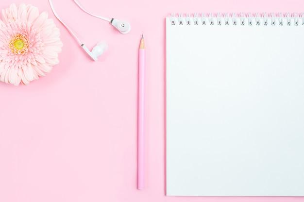 Spazio di lavoro: blocco note, matita, cuffie e fiore gerbera su sfondo rosa.