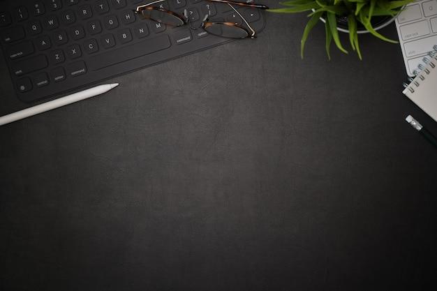 Spazio di lavoro creativo di scrivania in pelle nera per ufficio e spazio di copia