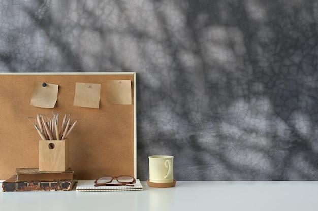 Spazio di lavoro dell'ufficio caffè, matita, libri e nota adesiva a bordo con lo spazio della copia.