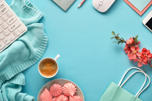 Spazio di lavoro femminile con maglione di cotone, tastiera, telefono cellulare, piatto di marshmallow e tazza di caffè