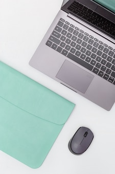 Spazio di lavoro lifestyle per studenti, impiegati, liberi professionisti. concetto di educazione moderna. computer portatile grigio in custodia blu e mouse wireless. vista dall'alto. disteso.