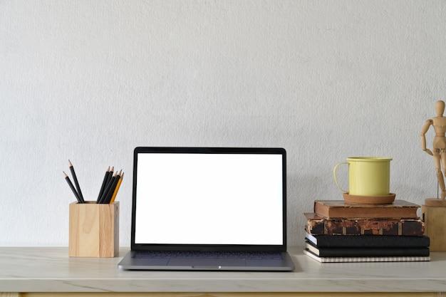 Spazio di lavoro loft con laptop schermo bianco vuoto e gadget creativo.