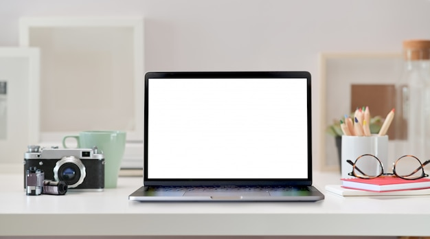 Spazio di lavoro loft con laptop schermo vuoto, macchina fotografica d'epoca e forniture per ufficio a casa
