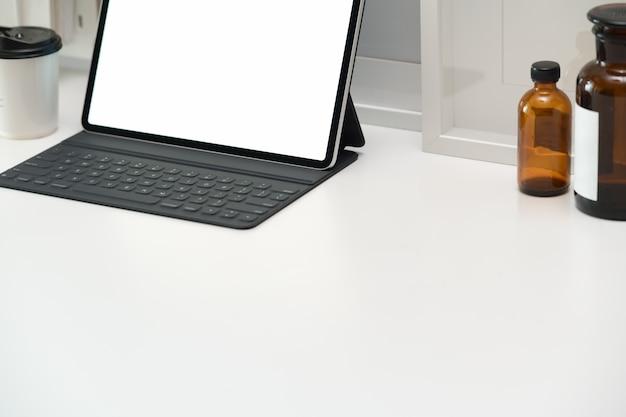 Spazio di lavoro minimo con tablet e tastiera intelligente