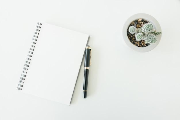 Spazio di lavoro minimo - foto piatta piano creativo della scrivania dello spazio di lavoro con lo schizzo e la matita di legno su priorità bassa bianca della copia spazio. vista dall'alto, fotografia piatta.