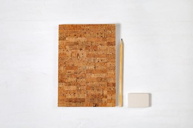 Spazio di lavoro per studente, per persona creativa, piccolo libro, matita di legno, gomma su sfondo chiaro con spazio di copia. vista dall'alto. disteso.