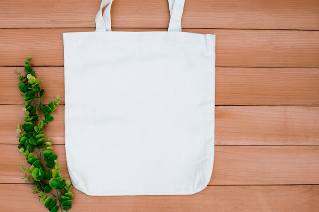 Spazio in bianco del modello del sacco di acquisto del panno di tela del tessuto della tela di canapa su backgroung di legno.