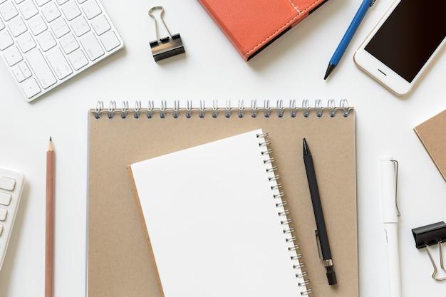 Spazio in bianco della copia della carta del calendario sul taccuino marrone sulla tavola moderna dell'ufficio con i rifornimenti