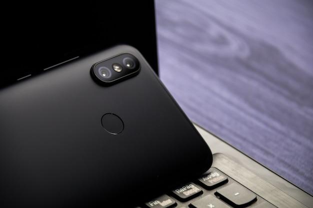 Spazio moderno della copia dello smartphone e del taccuino. cellulare con doppia fotocamera e lettore di impronte digitali
