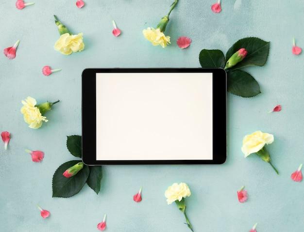 Spazio orizzontale della copia della compressa digitale circondato dai fiori