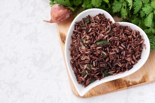 Spazio riso rosso biologico nel piatto cuore con cibo vegetale