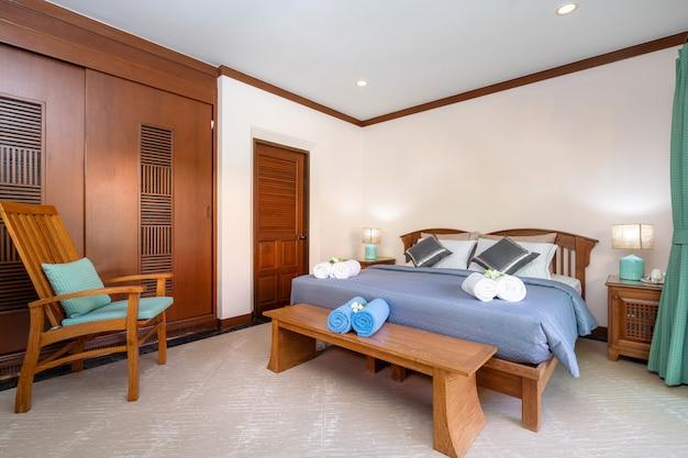 Spaziosa camera da letto con lenzuolo blu e wadrobe in legno