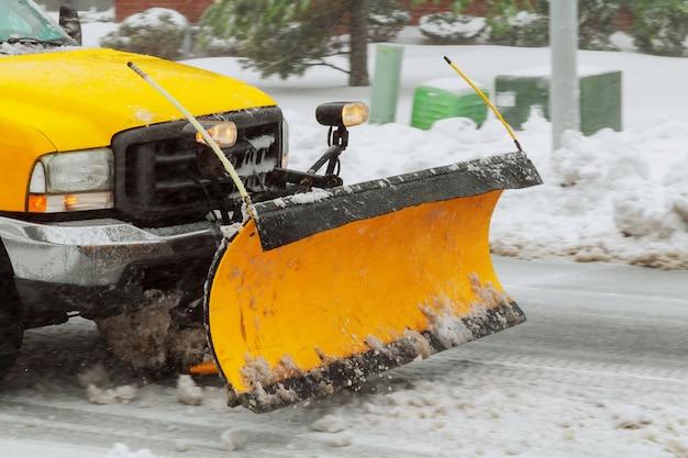 Spazzaneve che pulisce la neve dalla strada di città