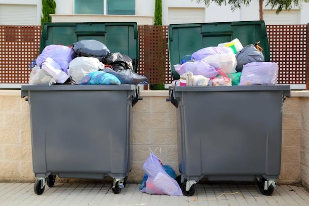 Spazzatura dell'immondizia contenitore pieno in strada