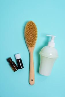 Spazzola anticellulite per massaggio corpo secco, sapone aromaterapico in una bottiglia bianca su un blu