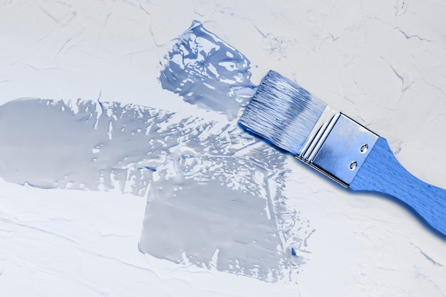 Spazzola con manico in legno con delicata vernice blu su sfondo bianco stucco strutturato. classico colore blu dell'anno 2020