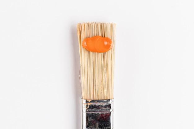 Spazzola con vernice arancione e sfondo bianco