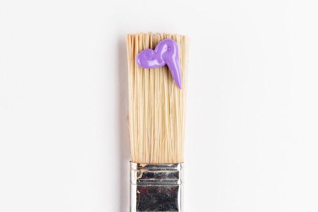 Spazzola con vernice viola e sfondo bianco