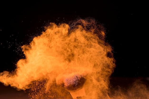 Spazzola cosmetica in nuvola di polvere di trucco su sfondo scuro
