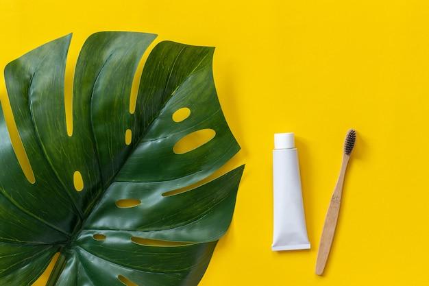 Spazzola di bambù naturale eco-compatibile, tubetto di dentifricio e monstera tropicale. impostare per il lavaggio