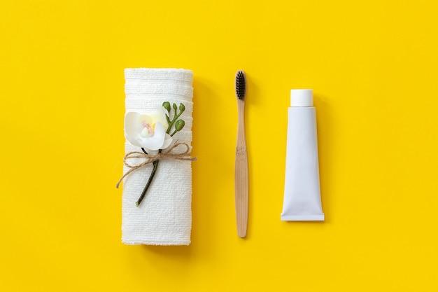 Spazzola di bambù naturale ecologica, asciugamano bianco e tubetto di dentifricio. impostare per il lavaggio