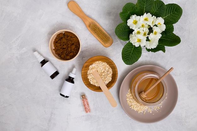 Spazzola di legno; miele; avena; salgemma himalayano; bottiglia di olio essenziale con vaso di fiori primula su sfondo concreto