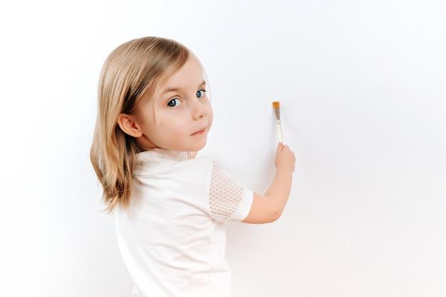 Spazzola di pittura della bambina sulla parete bianca