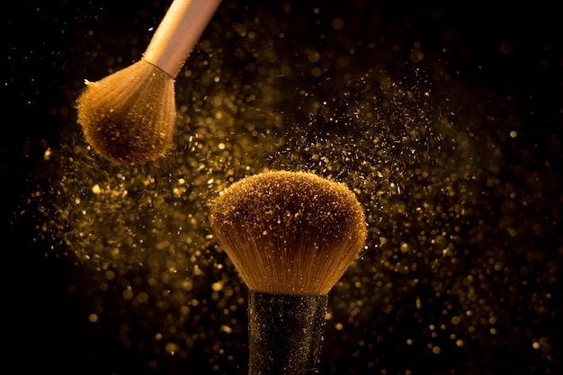 Spazzola di trucco con polvere cosmetica dorata che si spande su fondo nero
