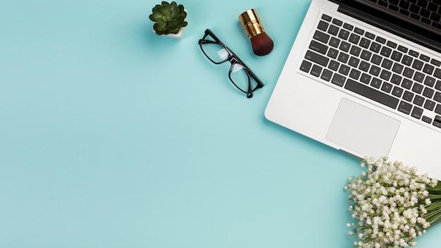 Spazzola di trucco, occhiali, mazzo del fiore bianco della pianta del cactus con il computer portatile su fondo blu