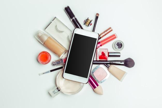Spazzola e cosmetici isolati su uno sfondo bianco. vista dall'alto.