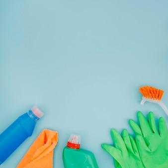 Spazzola; guanti verdi; tovagliolo e bottiglia su sfondo blu