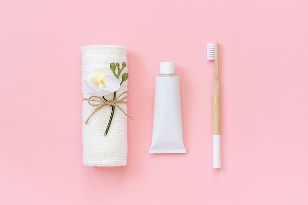 Spazzola in bambù naturale ecologico, asciugamano bianco e tubetto di dentifricio.