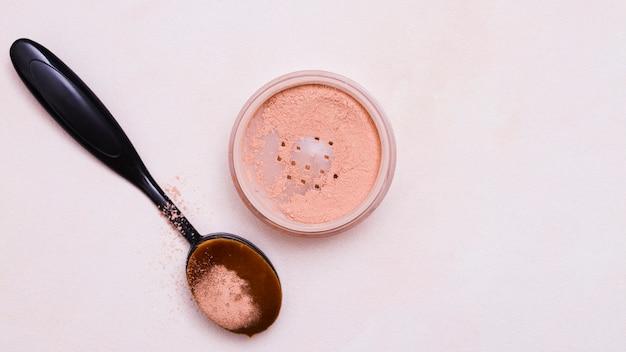 Spazzola ovale nera e cipria su sfondo rosa