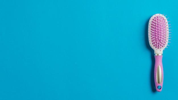 Spazzola per capelli rosa su sfondo blu