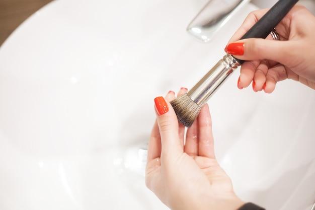 Spazzola per il trucco, donna che lava la spazzola per il trucco sporca con sapone e schiuma nel lavandino