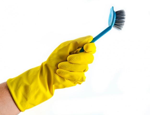 Spazzola per la pulizia in mano con guanti in lattice gialli isolati. concetto di pulizia