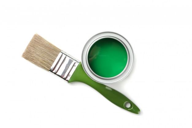 Spazzola verde e vernice isolate su superficie bianca