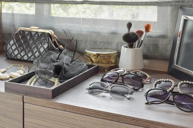 Spazzole della borsa, degli occhiali da sole, dei gioielli e di trucco su una toeletta di legno