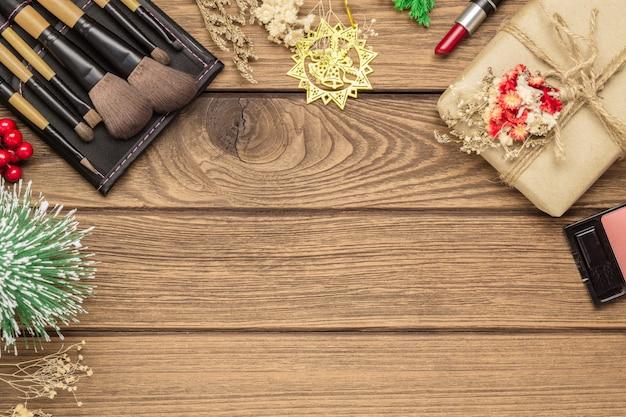 Spazzole di trucco della donna, rossetto e ornamenti di natale su legno