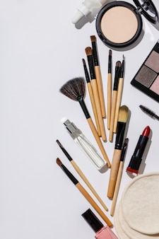 Spazzole di trucco e prodotti cosmetici su un bianco