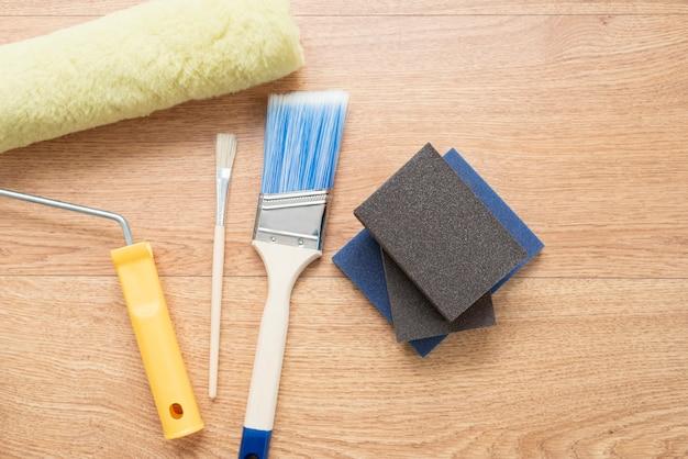 Spazzole e rulli di pittura su fondo di legno. strumenti di costruzione per la verniciatura di superfici