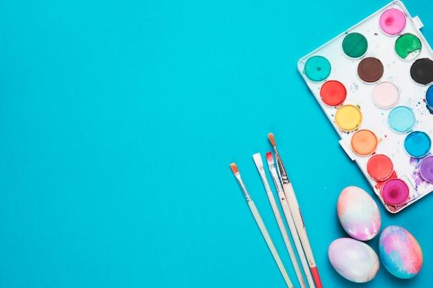 Spazzole; uova di pasqua dipinte e tavolozza di plastica con colori ad acqua su sfondo blu
