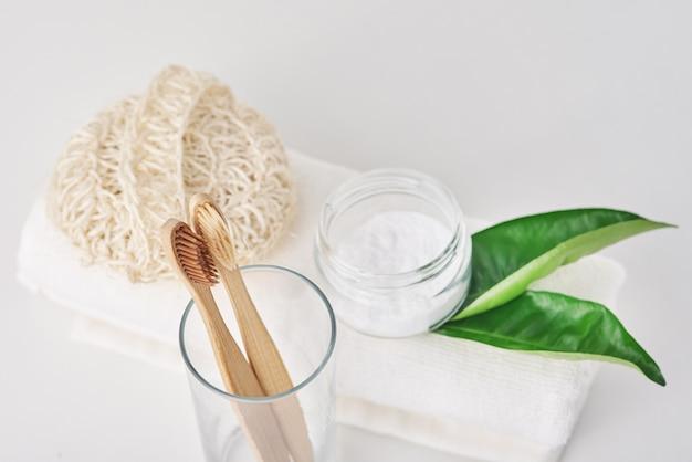 Spazzolini da denti di bambù di legno in vetro, bicarbonato di sodio e asciugamano su bianco.